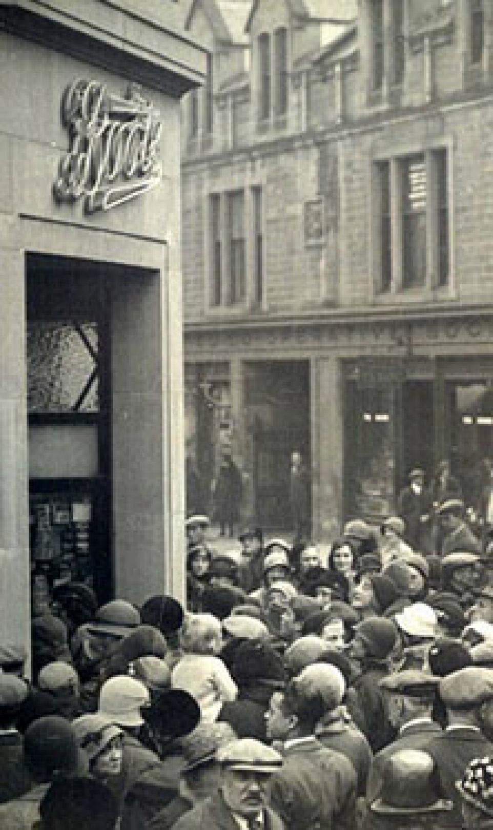 Black and white photo of a big crowd, gathering outside of the 1000th Boots store in the UK on its opening day
