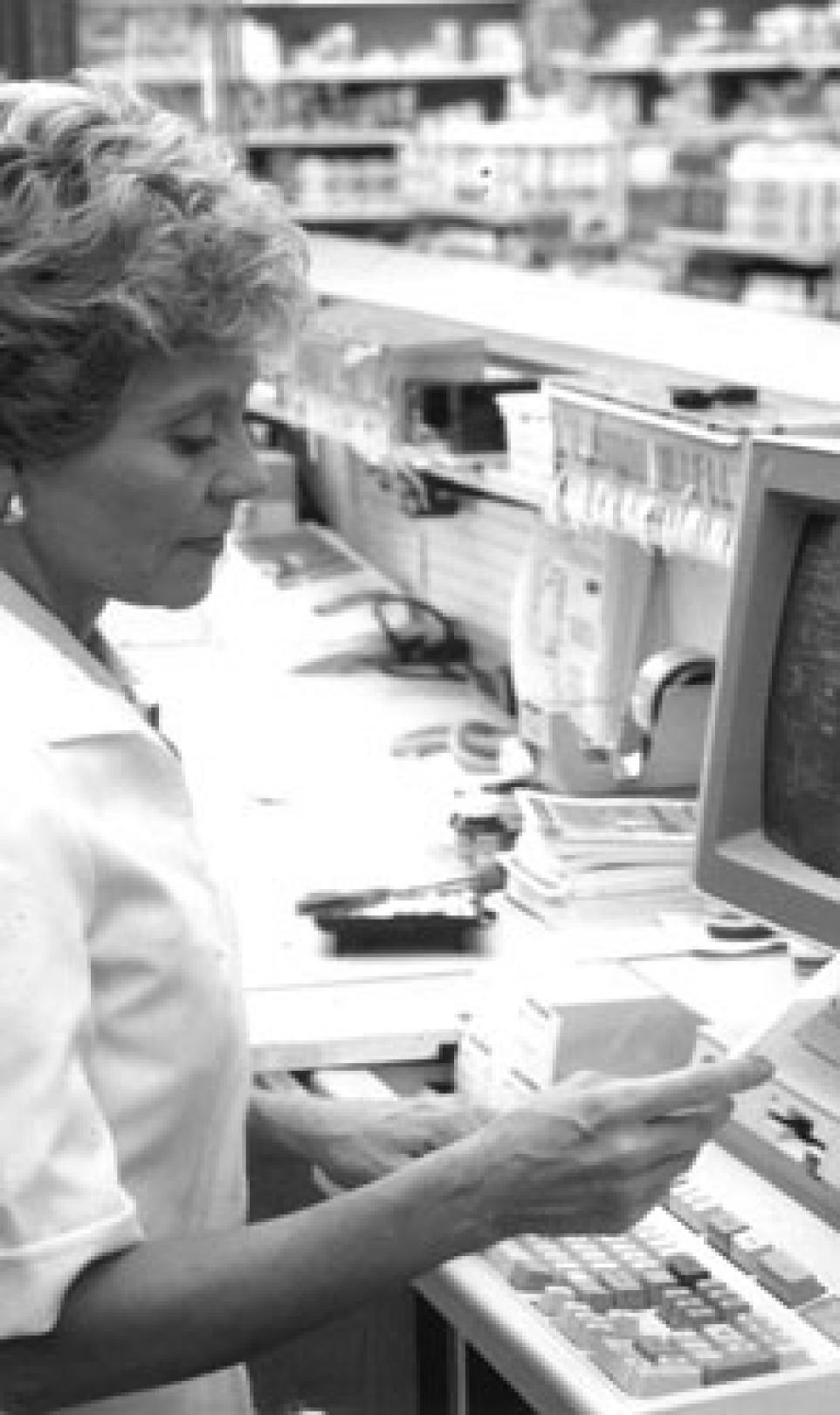 Black and white photograph showing a female employee, operating one of the first Intercom pharmacy computers behind the till of a Walgreens store