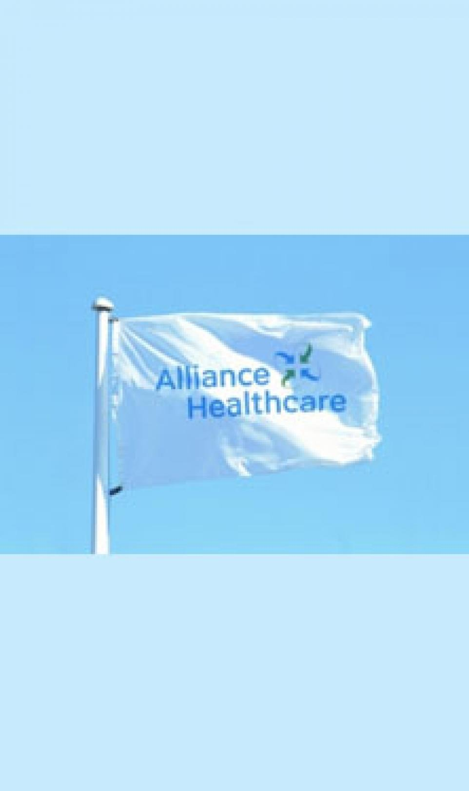 A white flag, blowing in the wind, featuring the blue and green Alliance Healthcare logo