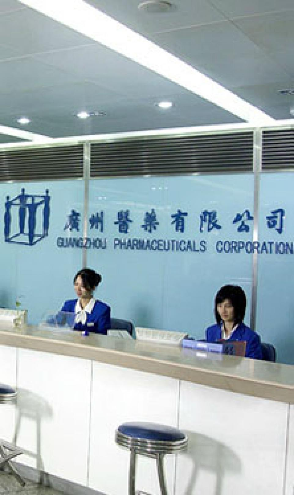 Two female receptionists in blue uniforms, pictured in the reception area of the Guangzhou Pharmaceuticals Corporation
