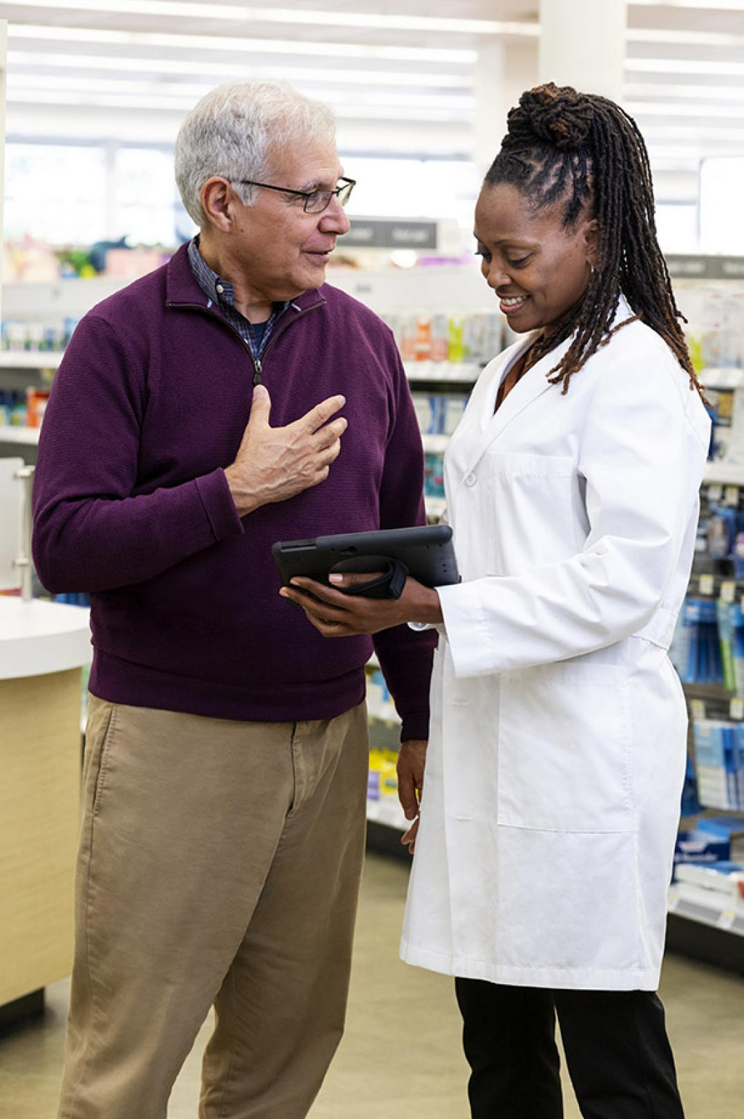 Pharmacist speaking with patient in store