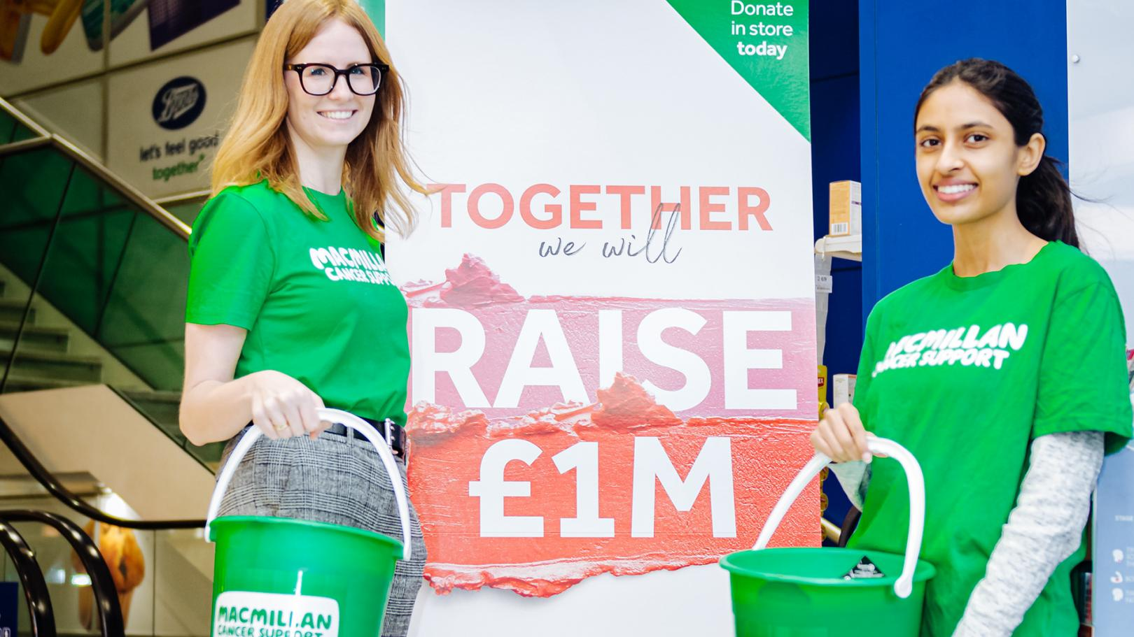Two MacMillan volunteers holding donation buckets smiling at the camera